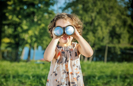 Portrait of a cheerful, little girl looking through the binoculars