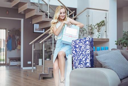 Abbastanza giovane signora che unboxing i suoi sacchetti della spesa