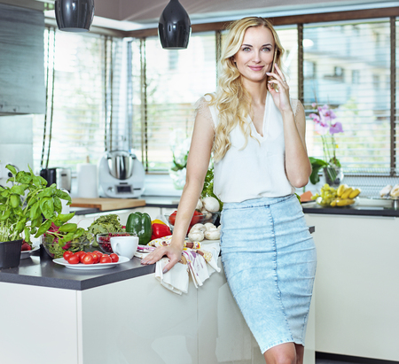 Pretty, blond woman realxing in the summer kitchen