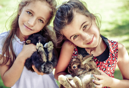 Two cheerful girls hugging fluffy rabbits