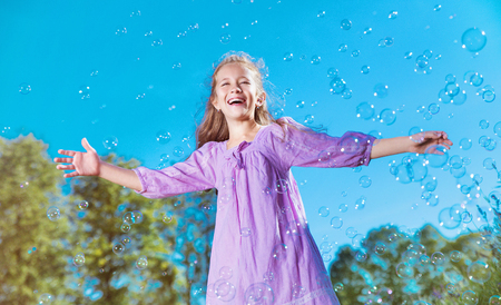 Cute, cheerful girl among lots of soap bubbles