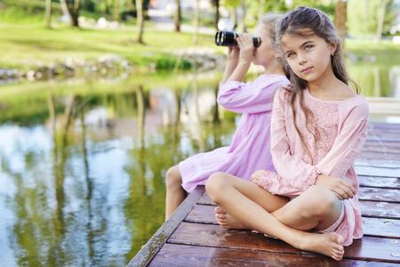 湿式桟橋 - 夏のショットの上に座って 2 人のリラックスした友人 写真素材