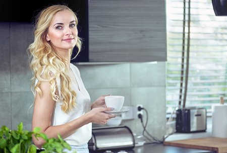 Ritratto di un adorabile, giovane donna che beve caffè