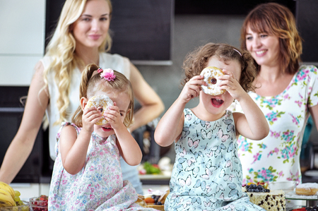 Pretty, cheerful women eating sweets with their children Archivio Fotografico