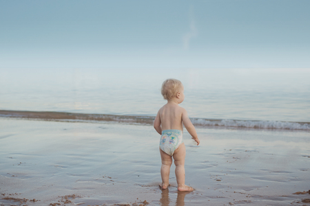 Cute, calm baby watching an oceans wave