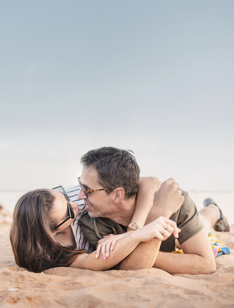 Portrait of a romantic, young couple relaxing on a beach