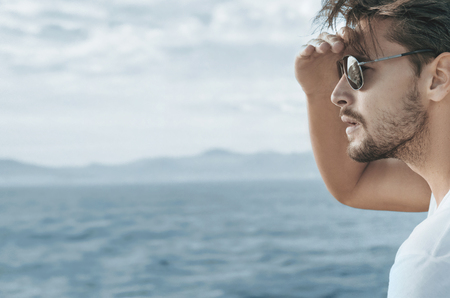 Profile portrait of a handsome guy relaxing on the boat