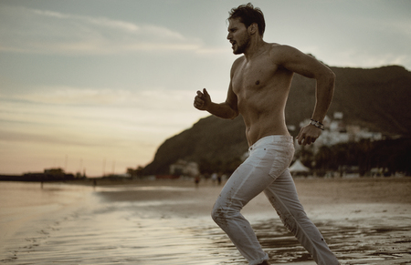 Handsome athlete running along the seaside Stock Photo