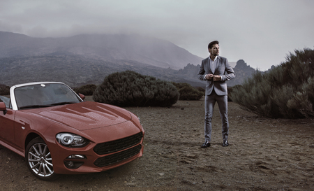 Young businessman standing next to the luxurious convertible