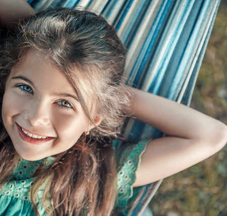 Cheerful, young girl resting on the hammock 版權商用圖片