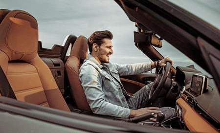 Przystojny, młody mężczyzna jadący luksusowym kabrioletem