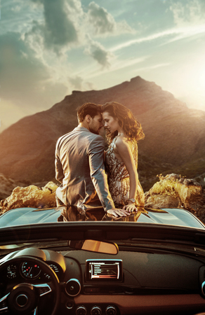 Romantic, young couple sitting on the bonnet Standard-Bild - 93723559