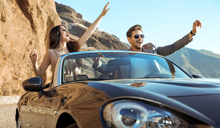 Smart, relaxed couple riding a luxurious convertible Banque d'images