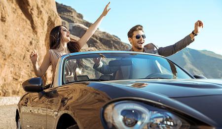 Smart, relaxed couple riding a luxurious convertible Standard-Bild