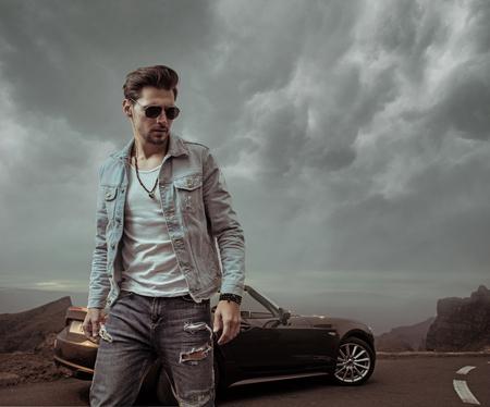 Handsome guy posing next to the luxurious convertible car Foto de archivo