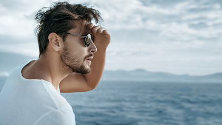 Portrait of a handsome guy watching ocean waves