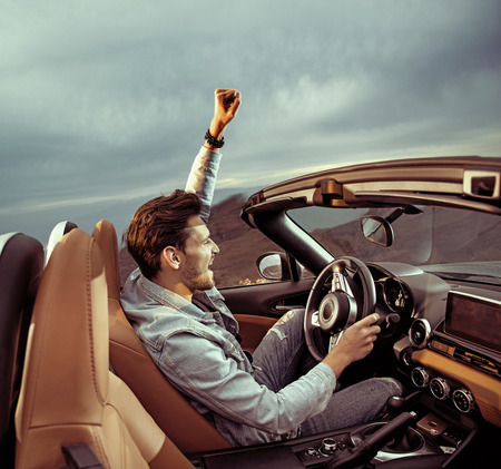 Handsome, young man riding a luxuriois convertible car Zdjęcie Seryjne