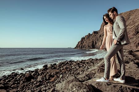 Elegante, jovens amantes assistindo as ondas do oceano Foto de archivo