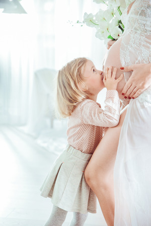 Little daughter kissing her pregnant mothers belly