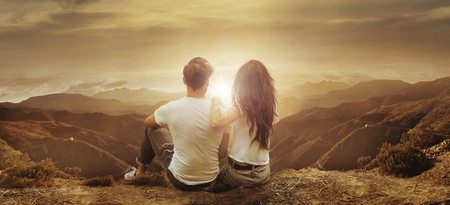 Young, relaxed couple watching a beautiful sunset Archivio Fotografico