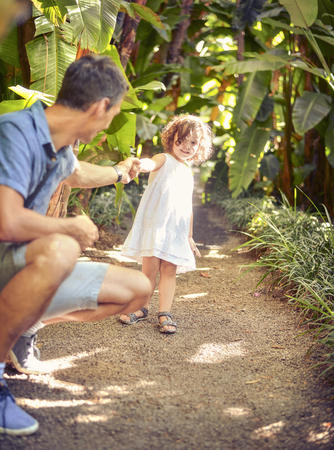 Father and daughter in the tropical garden