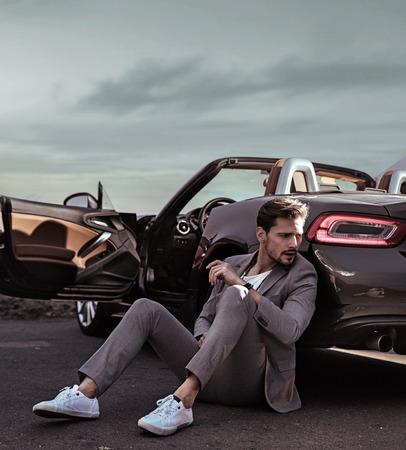 Elegant guy leaning on the luxurious car