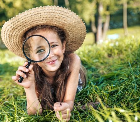 Hübsches Mädchen , das ein Vergrößerungsglas hält Standard-Bild - 93845901