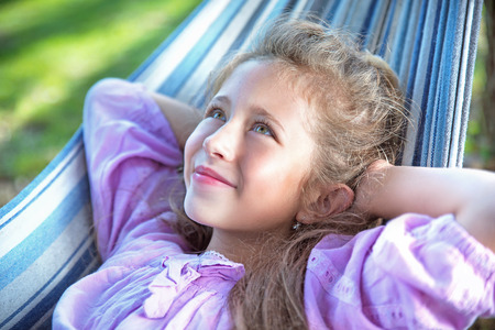 Cheerful, young girl resting on the hammock Archivio Fotografico