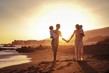 Relaxed family on a tropical beach, beautiful sunset Archivio Fotografico