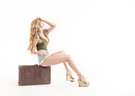Pretty blond lady sitting on the luggage, isolated