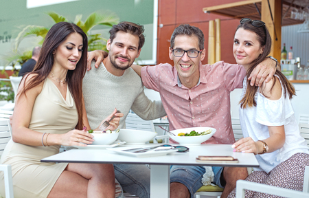 Portrait of cheerful, young freinds in the summer restaurant Banco de Imagens