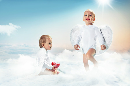 Conceptual portrait of a two cheerful cupids on the cloud Stock fotó
