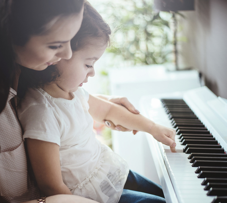 Mom teaching her little daughter piano playing Stock Photo