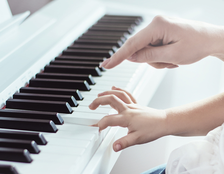 Closeup picture of two hands of mother and daughter playing piano