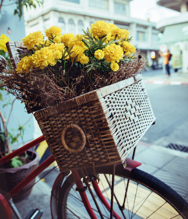 Closeup picture of a vintage bike with yellow flowers in a basket Foto de archivo - 101345335