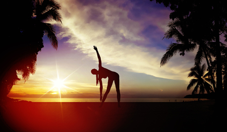 Flexible woman training on a tropical beach Stock Photo