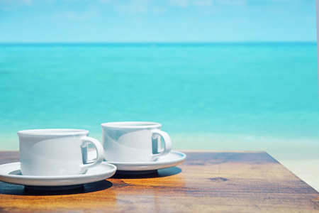 Two cups of hot coffee over a clear oceans water