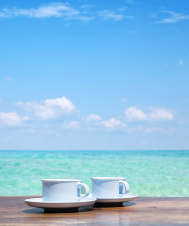 Two cups of hot coffee over a clear ocean's water Фото со стока - 102218716