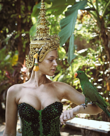 Asian queen holding a green parrot Stock Photo