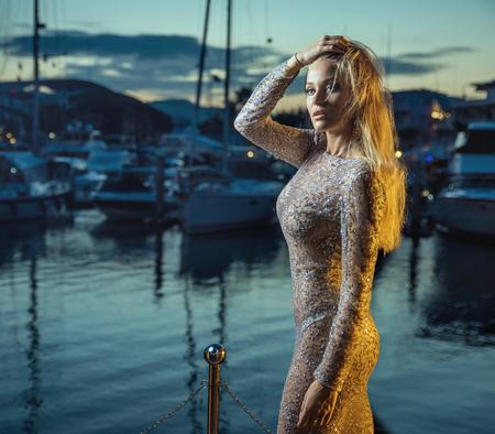 Elegant, sexy blonde walking in docks - vacation shot Standard-Bild