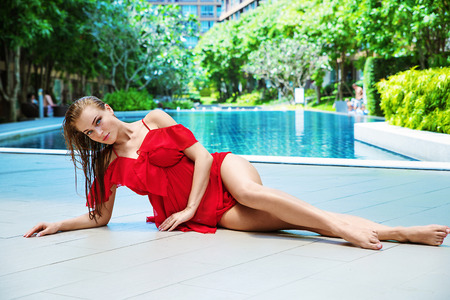 Blond cute lady relaxing by the swimming-pool Stock Photo