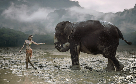 Conceptual portrait of a young, senusal tamer with an elephant 写真素材