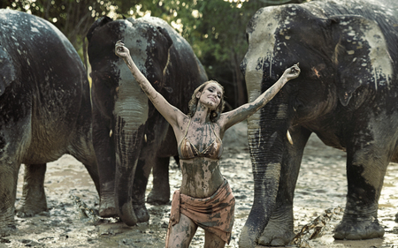 Sensual tamer playing with elephants in clay 写真素材