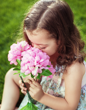 Pretty and cute child holding and sniffing flowers