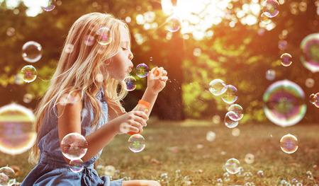 Retrato de un niño alegre soplando pompas de jabón