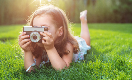 Cute little childl lying on green lawn and taking a picture Stockfoto