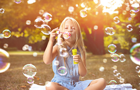 Portrait of a cheerful child blowing soap bubbles