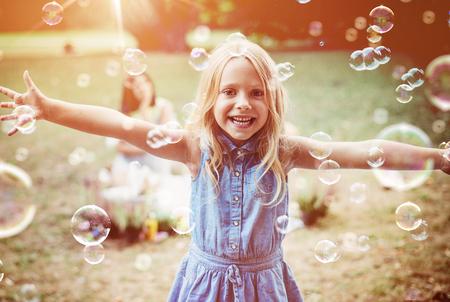 Cheerful, little girl enjoying bubble blowing Banco de Imagens