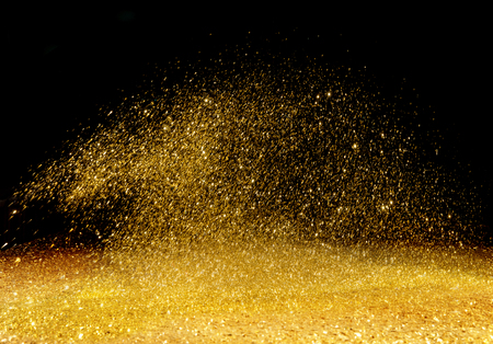 Golden, shining powder scattered over the dark background