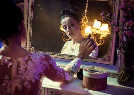 Portrait of a pretty, brunette countess touching an antique mirror Archivio Fotografico - 111767108